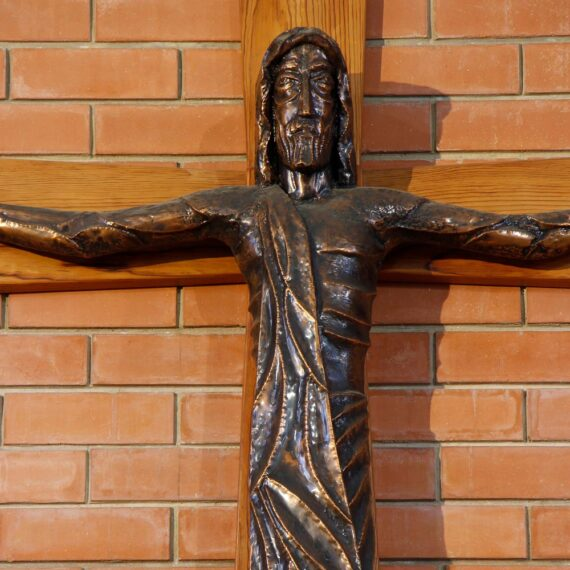 Copper Figure. 145cmH x 130cmW x 25cmD. Beaten copper with black oxide patina polished highlights. INRI letters Beaten copper, gold plated. Wooden Cross 247cmH x 240cmW x 4cmD.