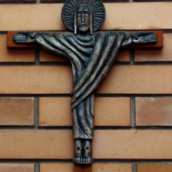 Cast Bronze with patina, polished highlights on wooden cross. 53cm H x 37cm W