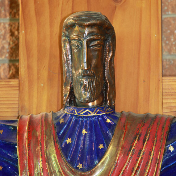 Beaten copper with black oxide patina, polished highlights and coloured and gold enamel, lacquered. Gold Leaf on INRI. Figure: 110cmH x 107cmW x 23cmD. Wooden cross: 182cmH x 182cmW x 14cmD